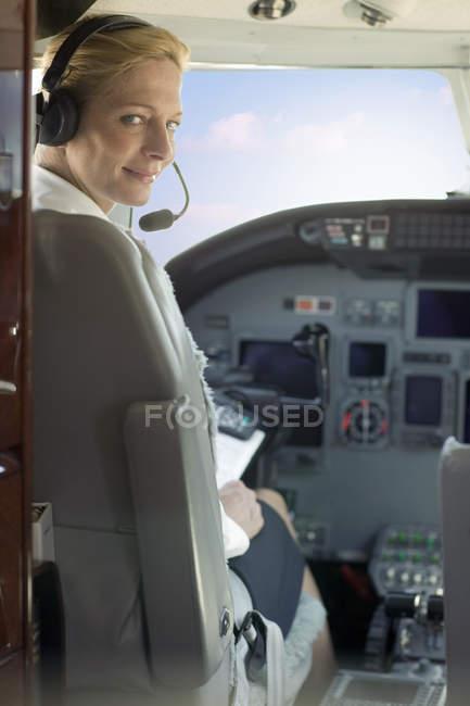 Портрет блондинка женщины экспериментальных носить наушники, глядя через плечо на камеру в кабине самолета — стоковое фото