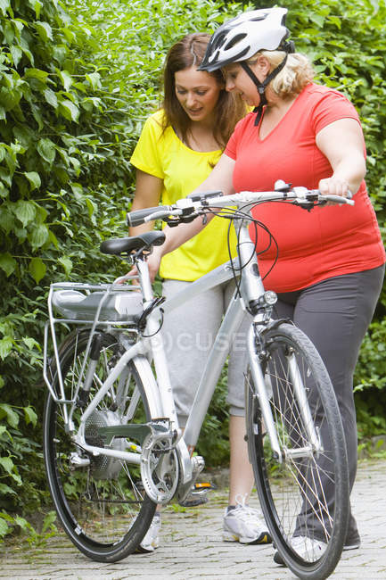 Two friends looking at silver bike outdoors — Stock Photo