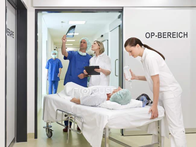 Medico ed infermiere prendendo il paziente in sala operatoria hospital e guardando alle radiografie — Foto stock