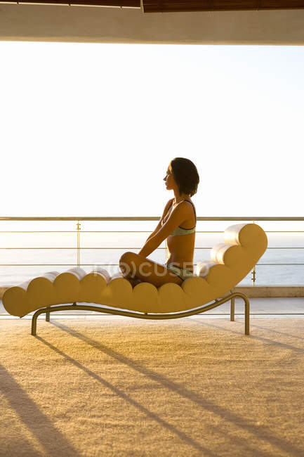 Jeune femme assise sur une chaise longue par balcon, vue latérale — Photo de stock