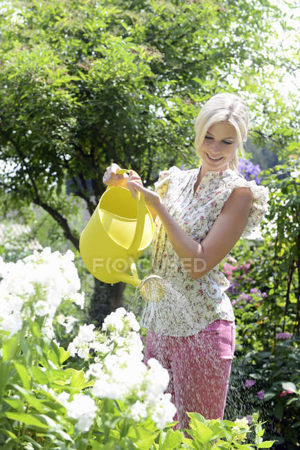 Mid adult woman watering flowers with yellow watering can — Stock Photo