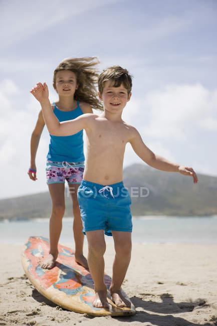 Boy and girl balancing on surfboard on beach — Stock Photo
