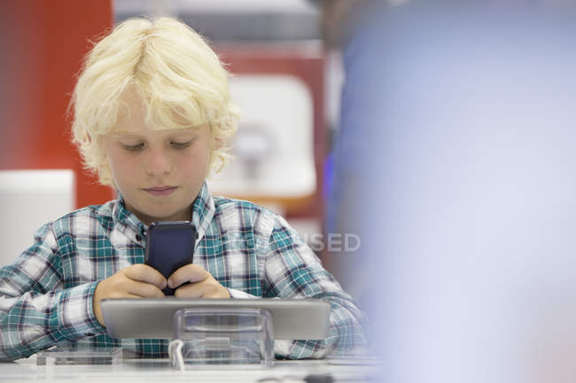 Boy looking at cell phone in electronics store — Stock Photo