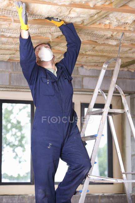 Man installing ceiling insulation — Stock Photo