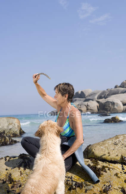 Woman in wetsuit on rock on beach, preparing to throw stick for dog — Stock Photo