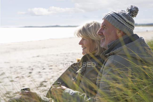 Vista lateral do casal sênior com copos na praia sorrindo — Fotografia de Stock