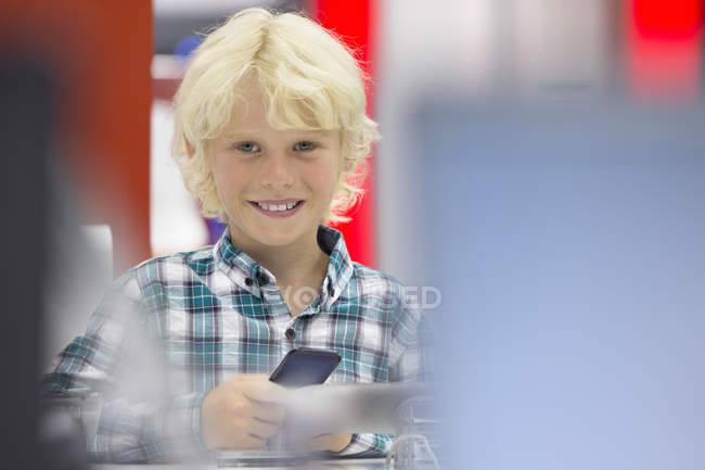 Portrait of smiling boy looking at cell phone in electronics store — Stock Photo