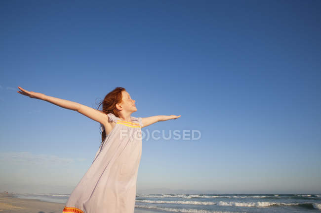 Happy girl with arms raised to sky on sunny beach — Stock Photo