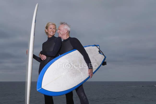 Senior man hugging mature woman in wetsuit on beach — Stock Photo