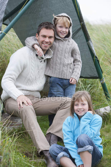 Father and children sitting near tent with grass on background — Stock Photo