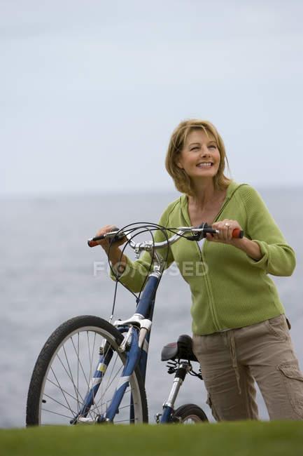 Поверхности уровня вид зрелой женщины с велосипедов на море — стоковое фото