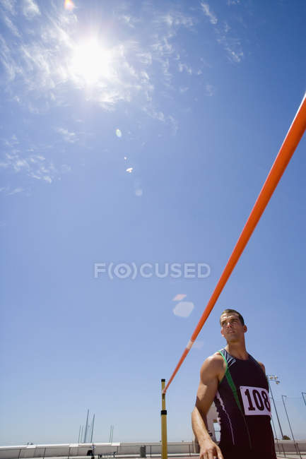 Young male athlete by bar, low angle view (lens flare) — Stock Photo