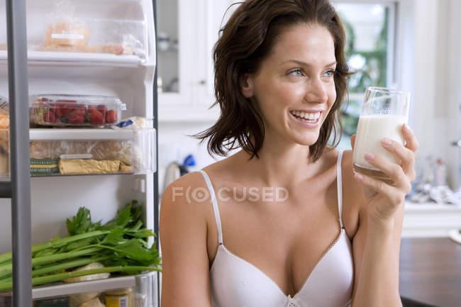 Giovane donna in biancheria intima con drink di porta aperta del frigo, sorridente — Foto stock