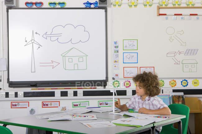 Curioso studente esaminando la turbina di vento di modello nell'aula della scuola — Foto stock