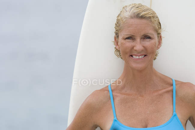 Portrait of smiling mature woman with surfboard — Stock Photo