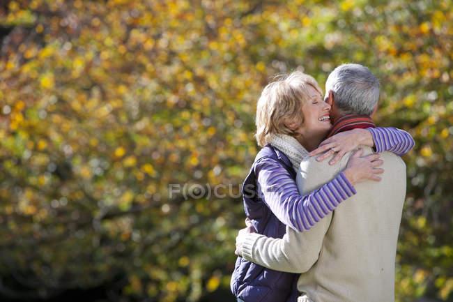 Романтична старший пара обіймає в Осінній Парк — стокове фото