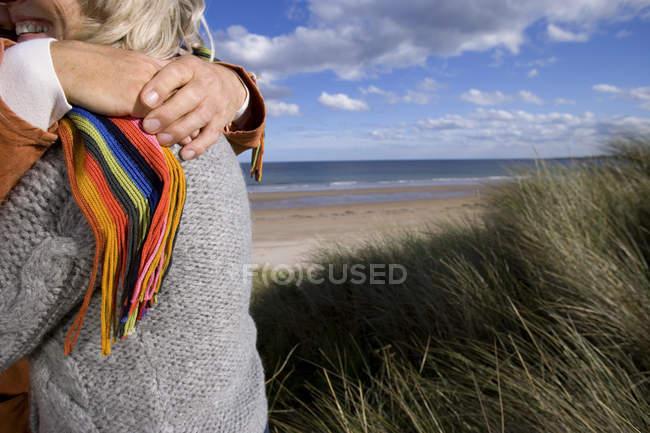 Casal sênior abraçando na duna de areia — Fotografia de Stock