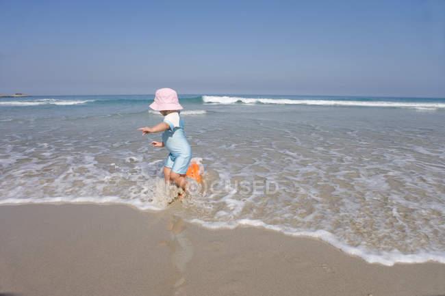 Fille avec chapeau rose jouant dans les vagues sur la plage — Photo de stock