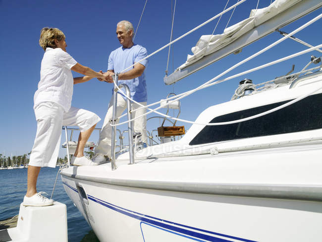 Senior man helping woman getting onto boat — Stock Photo