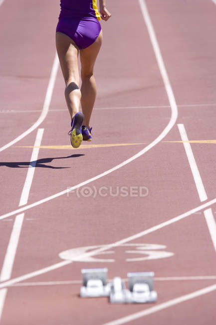 Rear view of female athlete running on race track — Stock Photo