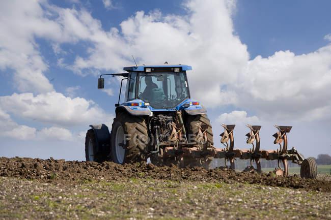 Champ de labourage agriculteur avec tracteur — Photo de stock