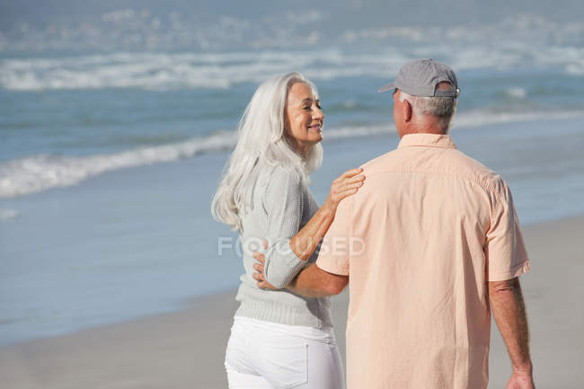 Senior couple hugging and walking on sunny beach — Stockfoto