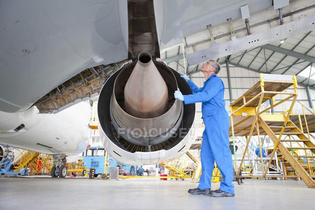 Инженер, осмотр двигателя на пассажирский самолет в ангаре — стоковое фото