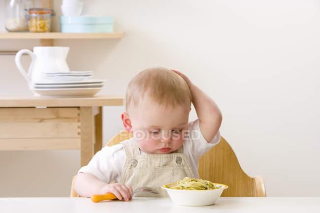 Olhando para o prato de macarrão e coçar a cabeça do bebê — Fotografia de Stock