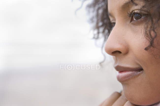 Vista laterale della donna sorridente con sfondo sfuocato — Foto stock