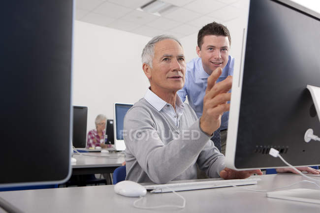 Teacher talking with adult student in college evening class computer lab — Stock Photo