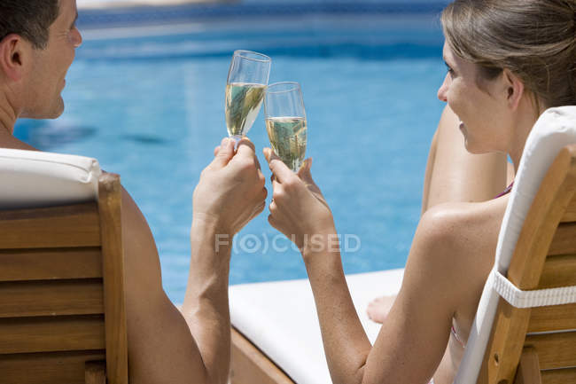 Couple on lounge chairs toasting champagne flutes at poolside — Stock Photo