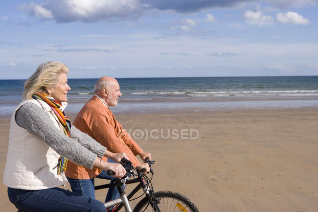 Senior couple cycling on beach, side view — Stock Photo