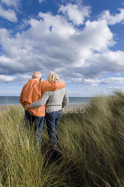 Casal sênior braço dado na duna de areia, olhando para o mar — Fotografia de Stock