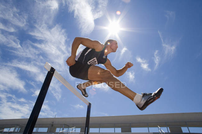 Male athlete jumping over hurdle, low angle view (lens flare) — Stock Photo