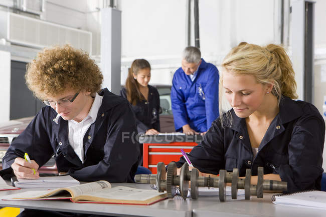 Students with auto part studying automotive trade in vocational school — Stock Photo