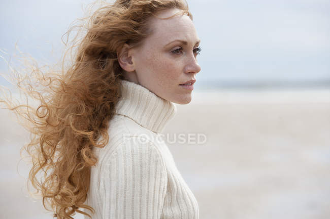 Side view of woman with ginger curly hair in white sweater on beach — Stock Photo