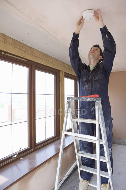 Electrician standing on ladder and installing detector — Stock Photo