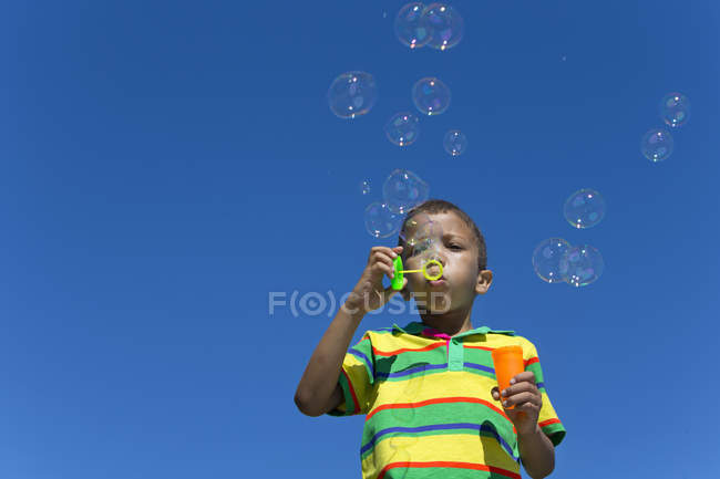 Boy blowing bubbles with bubble wand — Stock Photo