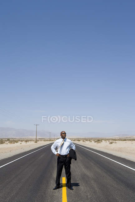 Businessman standing on line in middle of road in desert with hands on hips — Stock Photo