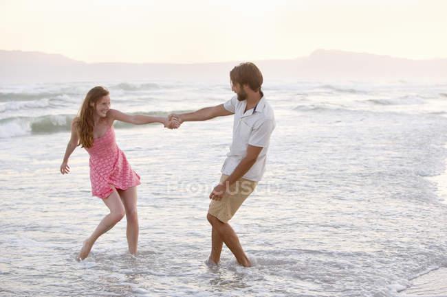 Casal romântico andando na praia ensolarada no dia — Fotografia de Stock
