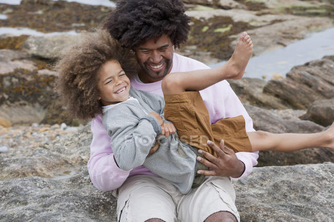 Happy son on hands of father on rocky beach — Stock Photo