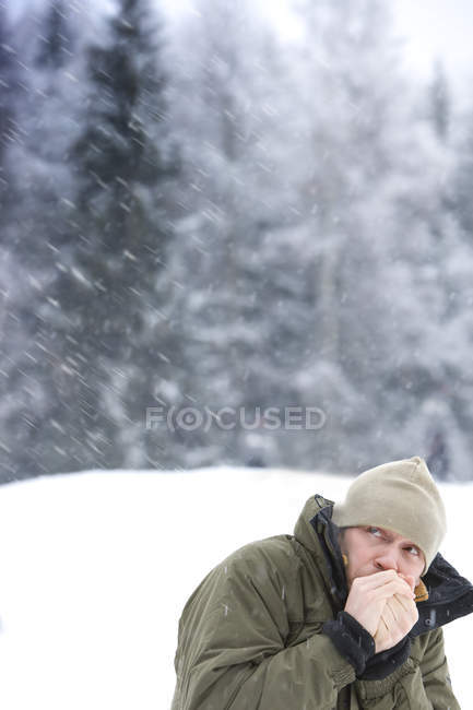 Metà di uomo adulto scalda le mani a tempo nevoso — Foto stock