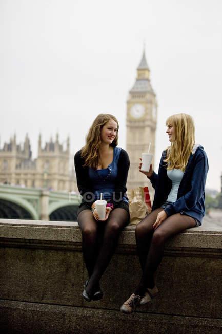 Deux adolescentes s'asseyant près de Big Ben, déjeunant — Photo de stock