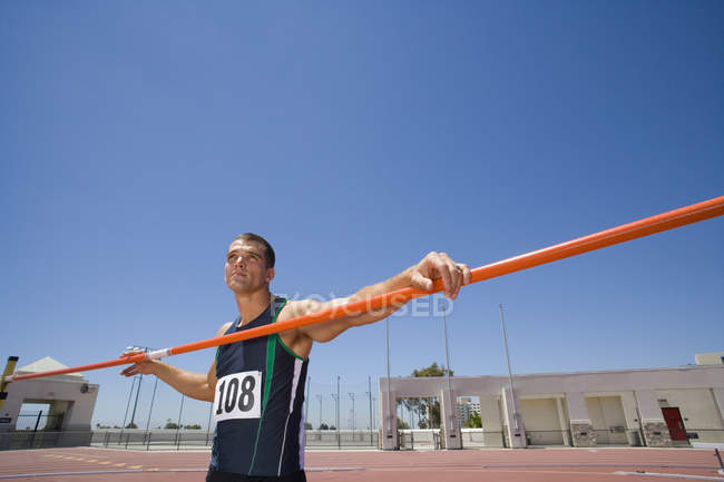 Male athlete with pole, low angle view (lens flare) — Stock Photo