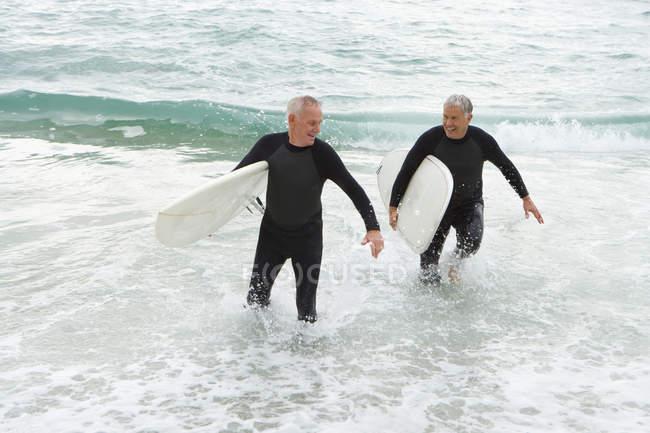Surfeurs mâles en néoprène dans l'eau sur la plage — Photo de stock