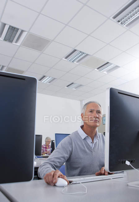 Adult student studying in college evening class in computer lab — Stock Photo
