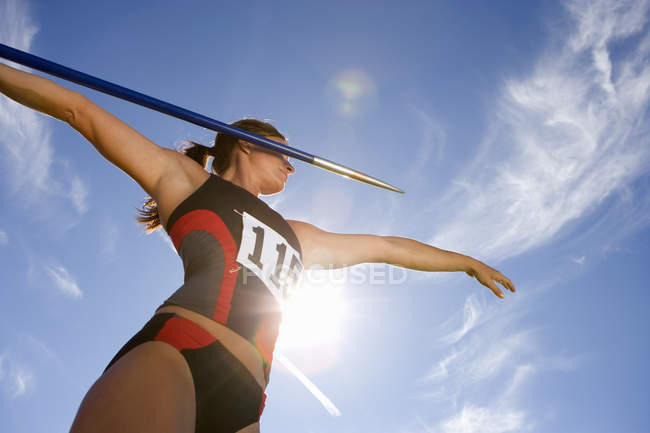 Low angle view of female athlete preparing to throw javelin, lens flare — Stock Photo