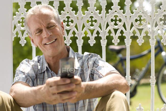Usando o telefone celular ao ar livre, sentado contra cerca de homem maduro — Fotografia de Stock