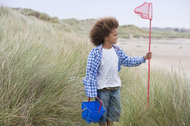 Chico de raza mixta de pie en la playa con cubo y red - foto de stock