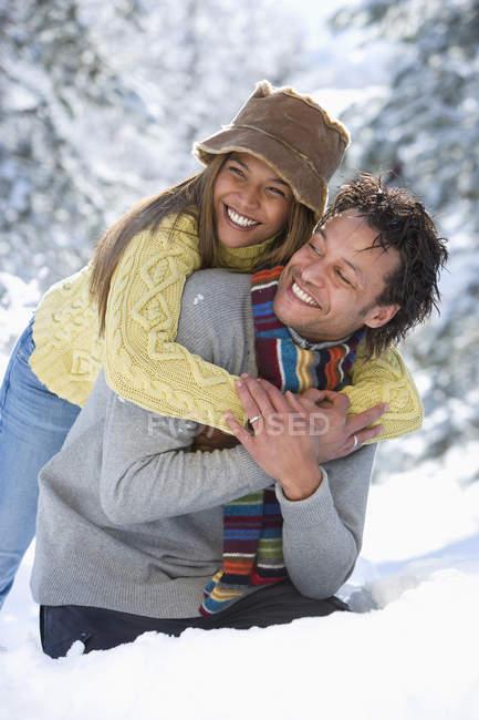 Retrato de raza mixta pareja abrazándose en la nieve - foto de stock